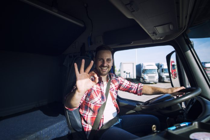 Truck driver loving his job and showing okay gesture sign while sitting in his truck cabin. Transportation services.