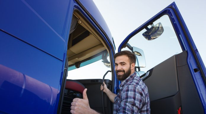 Professional truck driver entering his truck long vehicle and holding thumbs up.