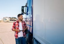 truck-driver-casual-clothes-standing-by-his-truck-with-tablet-looking-truck