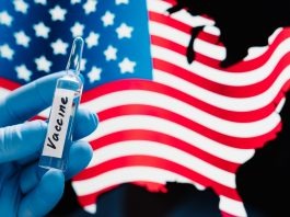 Hand in rubber medical gloves holding vaccine against coronavirus, USA flag in background